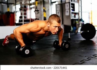 Young muscular athlete doing pushups