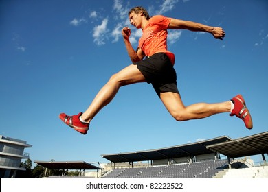 young muscular athlete is running  at the stadium background of blue sky