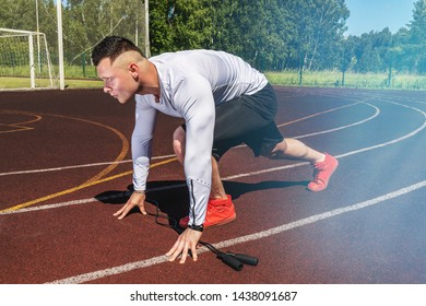 young muscular athlete is at the start of the treadmill at the stadium. Space for text
