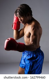 Young muscular athletic male boxer wearing blue boxing shorts and red boxing gloves. Fighter is on a grey background.