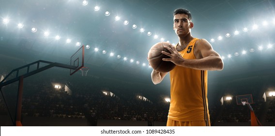 Young muscular basketball player holding a ball on floodlight professional basketbal court