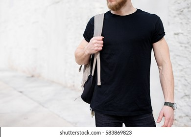 Young muscular bearded man wearing black tshirt and backpack posing outside. Empty white concrete wall on the background. Hotizontal mockup, front view.