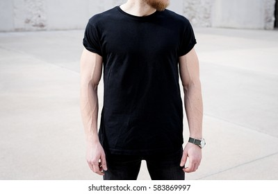 Young muscular bearded man wearing black tshirt and jeans posing in center of modern city. Empty concrete wall on the background. Hotizontal mockup, front view.