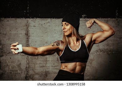 Young muscular beautiful woman is resting after training at the gym making selfie with smartphone.