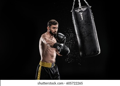 Young muscular boxer exercising with punching bag  isolated on black