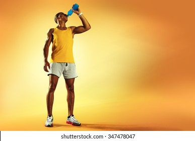 Young muscular build man drinking water of bottle after running, attractive athlete resting after workout outdoors, fitness and healthy lifestyle concept. Isolated on yellow