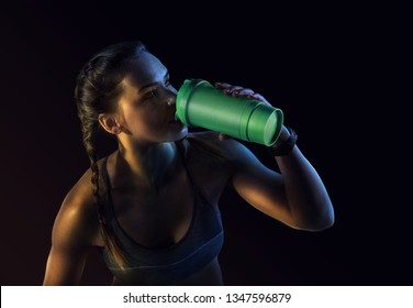 Young muscular build woman silhouette drinking water of bottle. Attractive athlete resting after workout outdoors, fitness. Isolated on black. Dramatic colorful close-up portrait.