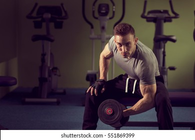 Young muscular built athlete working out in a gym, sitting on a weightlifting machine and lifting two dumbbells