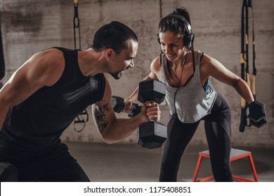 Young muscular couple doing hard exercise with dumbbells for shoulders on training at the gym.