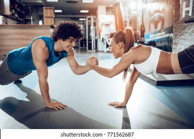 Young muscular couple doing doing hard workout at the gym.
