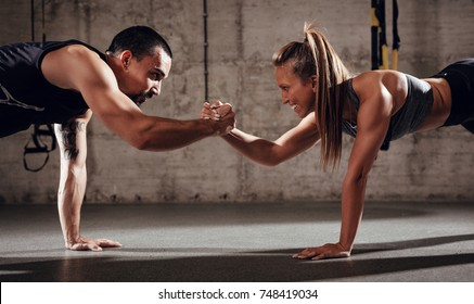 Young muscular couple doing strength exercise workout.