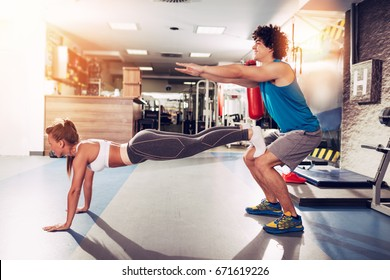 Young muscular couple having workout together at the gym. Handsome boy doing squats exercise, his cute girlfriend doing push-up.
