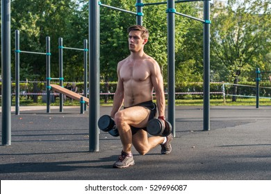 Young muscular fitness male model doing dumbbell lunge exercises in the park.