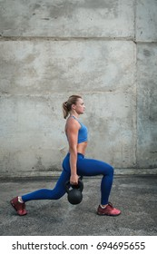 Young muscular girl in training makes lunges and holds weights in hands.