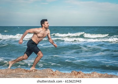 Young muscular guy, with a bare torso running along the beach