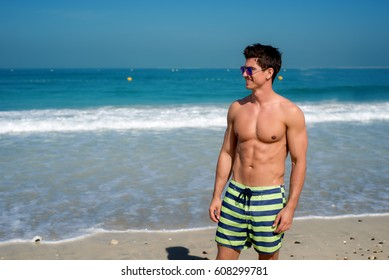 Young muscular guy in striped beach shorts sunbathing at bright beach. Beautful ocean view.