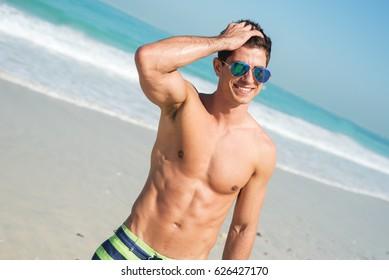 Young muscular guy in striped beach shorts sunbathing at bright beach. Beautful ocean view.