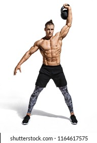 Young muscular guy training with kettlebell. Photo of handsome man with naked torso on white background. Strength and motivation. Full length