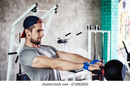 young muscular hipster athlete puts palm protection grips on. fitness, bodybuilding concept. Focus on face. Sport equipment