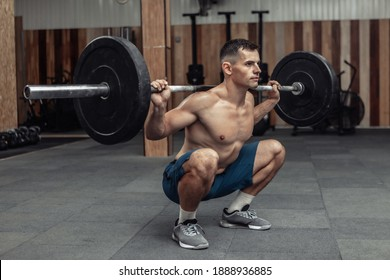 Young muscular male bodybuilder doing squats with a barbell on his shoulders in a modern health club. Bodybuilding and Fitness