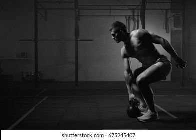 Young muscular man doing exercises with kettlebell in gym. Weightlifting workout. Sports, fitness concept. Black and white image.