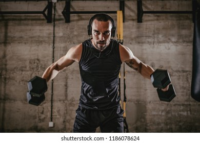 Young muscular man doing hard exercise with dumbbells for shoulders on training at the gym.