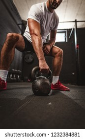 Young muscular man doing hard exercise with kettlebell on cross training at the gym.