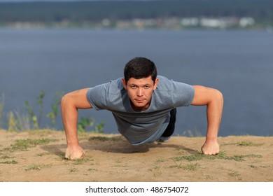 young muscular man doing push-ups outdoors