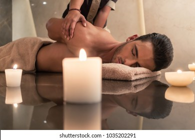 Young muscular man enjoying the healing benefits of traditional Thai massage at luxury spa and wellness center