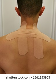 Young muscular man with kinesiology taping on his back to fix his upper trapezius sprain condition. Back tension and tightness treated by kinesiology tape around shouder area.