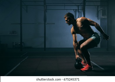 Young muscular man with naked torso working out in gym. Athletic male adult exercising with kettle bell. Fitness, sports concept.