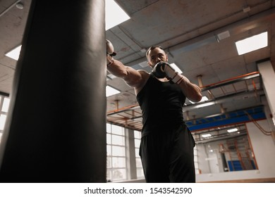 young muscular man performing blows on punch bag, close up lov angle view