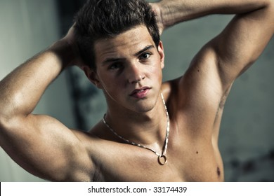 Young muscular man portrait. On wall background.