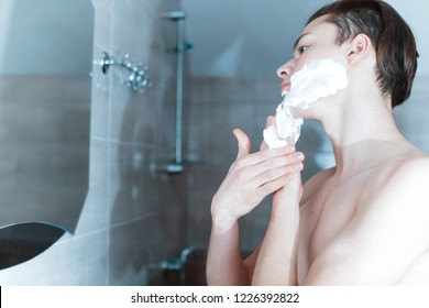 Young muscular man shaving over gray background