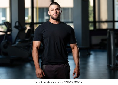 Young Muscular Man In Shorts And Black T-shirt Posing In Fitness Center