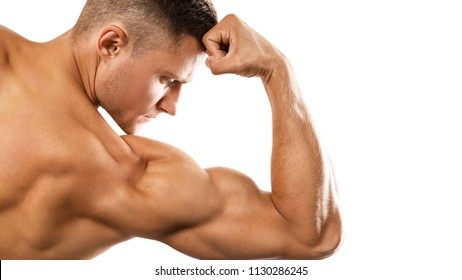 Young muscular man showing his bicep on white background