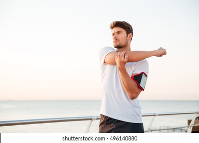 Young muscular man stretching his arms while standing at the seaside