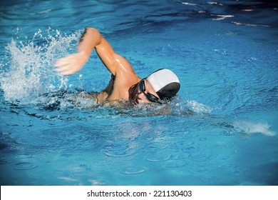 Young muscular man swimming the crowl style in swimming pool.