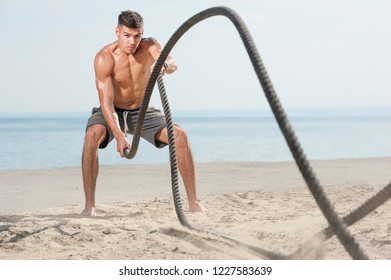 Young muscular man training with battle ropes on the beach against blue sky. Cross strength or functional training. Place for text.