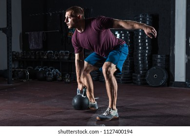 Young muscular man training with kettlebells. Strength and motivation
