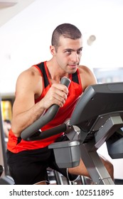 Young muscular man training on the cycle in the gym