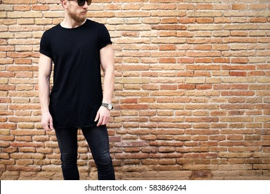 Young muscular man wearing black tshirt,sunglasses and jeans posing outside. Empty brown grunge brick wall on the background. Hotizontal mockup