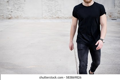 Young muscular man wearing black tshirt and jeans walking on the urban district. Blurred background. Hotizontal mockup
