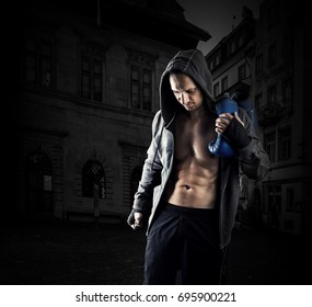 Young muscular men boxer wearing jacket with hood. Boxing gloves slung over his shoulder walk along night street of dark city.