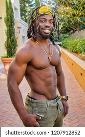 Young muscular shirtless African American man posing and smiling.