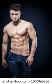Young muscular shirtless man with denim shorts on dark background