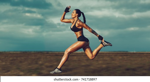 Young muscular sports woman running fast on summer field. Tattoo on body. Background blurred motion.