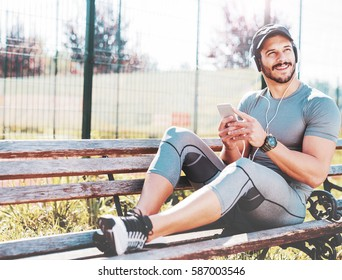 Young muscular sportsman sitting on a bench after fitness training and listening to music on a smart phone with headphones. Sport and recreation, fitness concept
