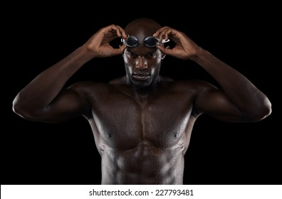 Young muscular swimmer wearing goggles against black background. Health and fitness concept.