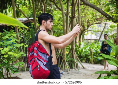 Young muscular topless man with backpack and phone, taking photo, looking away on background of tropical forest.